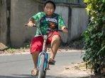 bonek-cilik-deni-asal-mataram-lombok-barat-saat-mengayuh-sepeda-ontelnya-penggemar-persebaya.jpg