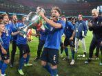 gelandang-italia-manuel-locatelli-merayakan-dengan-trofi-kejuaraan-euro-2020.jpg