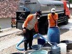 petugas-bpbd-tulungagung-menyalurkan-bantuan-air-bersih-pada-warga-ilustrasi-kekeringan-tulungagung.jpg