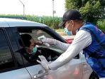 petugas-memeriksa-suhu-tubuh-pelaku-perjalanan-di-pos-penyekatan-jembatan-timbang-ngantru.jpg