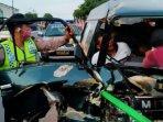 polisi-dan-warga-membantu-pengemudi-yang-terjepit-seusai-mobilnya-menabrak-truk-di-tulungagung.jpg