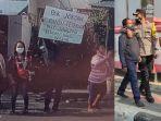 polisi-membawa-pria-yang-membentangkan-poster-ke-arah-presiden-joko-widodo.jpg