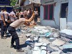 polisi-saat-berusaha-merobohkan-yang-sudah-rusak-akibat-terkena-dampak-gempa-senin-1242021.jpg