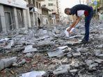 pria-mengais-puing-puing-gedung-klinik-yang-diserang-israel.jpg