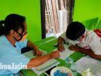 rahayu-hati-ibu-dari-akbar-siswa-sdn-bandulan-4-kota-malang-saat-menemani-anaknya-belajar.jpg