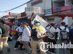 seorang-pria-bentangkan-spanduk-bertuliskan-sunblock-gratis-di-tengah-massa-aksi.jpg