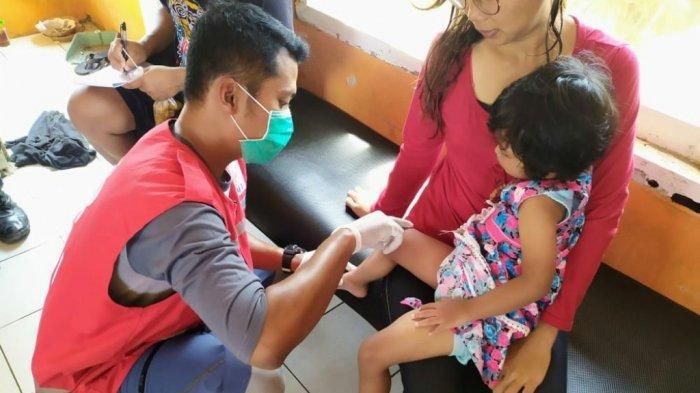 Petugas PMI tengah mengobati wisatawan balita yang tersengat ubur-ubur di Pantai Krakal, Tanjungsari, Gunungkidul pada Minggu (23/05/2021).