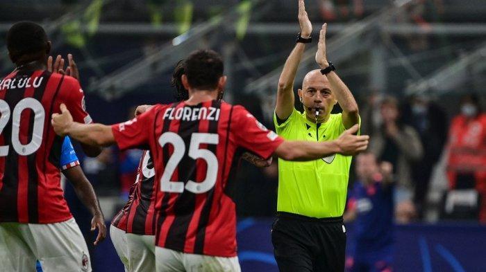 Wasit Cuneyt Cakir (kanan) memberi tanda ada pelanggaran di area penalti pada pertandingan sepak bola Grup B Liga Champions UEFA antara AC Milan dan Atletico Madrid pada 29 September 2021 di stadion San Siro.