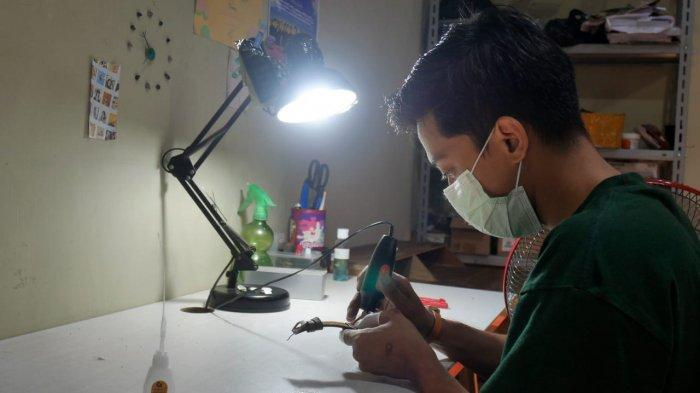 Afidha Fajar Adhitya saat merakit jam tangan kayu Eboni Watch di ruang kerja Eboni Watch di Desa Paseban, Kecamatan Bayat, Kabupaten Klaten, Minggu (21/3/2021).