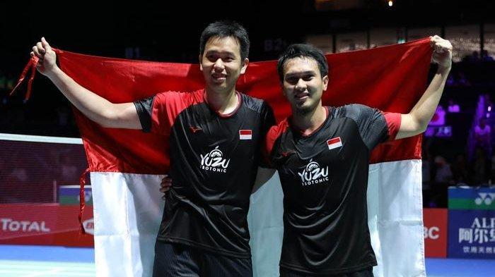 Pasangan ganda putra Indonesia, Hendra Setiawan dan Mohammad Ahsan, berpose dengan bendera Merah Putih usai memenangi medali emas Kejuaraan Dunia 2019 di Basel, Swiss, Minggu (25/8/2019).