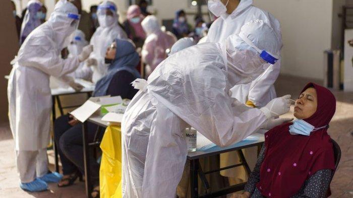 Pekerja medis mengumpulkan sampel usap dari seorang wanita selama pengujian virus corona di pusat pengujian Covid-19 di Kajang, pinggiran Kuala Lumpur, Malaysia Sabtu (8/5/2021) ditengah lonjakan kasus.