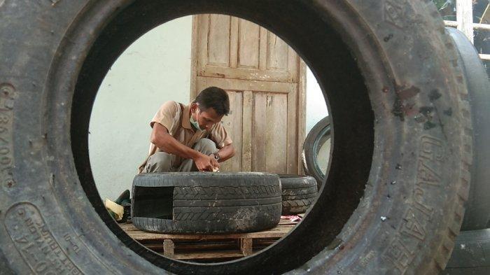 Dwi Hartono saat membuat akuarium dari ban bekas di rumahnya di Desa Sengon, Kecamatan Prambanan, Kabupaten Klaten, Senin (15/3/2021).