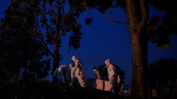 Petugas yang mengenakan APD membawa peti berisi jenazah dengan protokol COVID-19 di TPU Srengseng Sawah, Jakarta, Kamis (21/1/2021). TPU Srengseng Sawah yang baru sepekan dibuka untuk pemakaman dengan protokol COVID-19 dan menyediakan 541 liang lahat hampir penuh karena tingginya jumlah kematian akibat COVID-19.