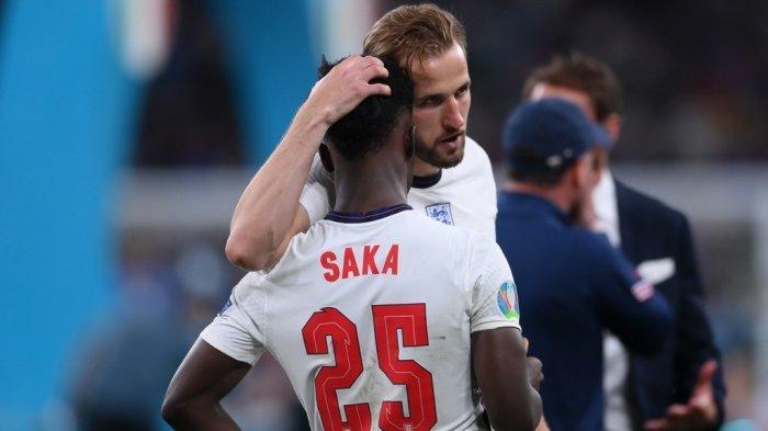 Kapten timnas Inggris, Harry Kane memberikan pelukan pada Bukayo Saka usai The Three Lions kalah adu penalti dari Italia pada partai final Euro 2020 di Stadion Wembley pada Minggu (11/7/2021) atau Senin dini hari WIB.