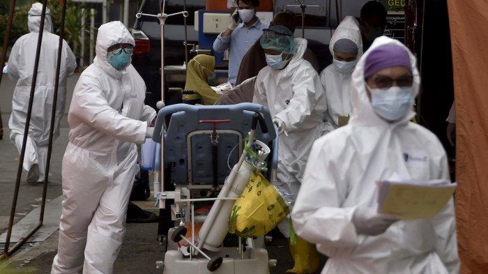 Petugas kesehatan mengenakan alat pelindung memindahkan seorang pasien yang dites positif virus corona Covid-19 ke sebuah rumah sakit di Bekasi pada 28 Juni 2021