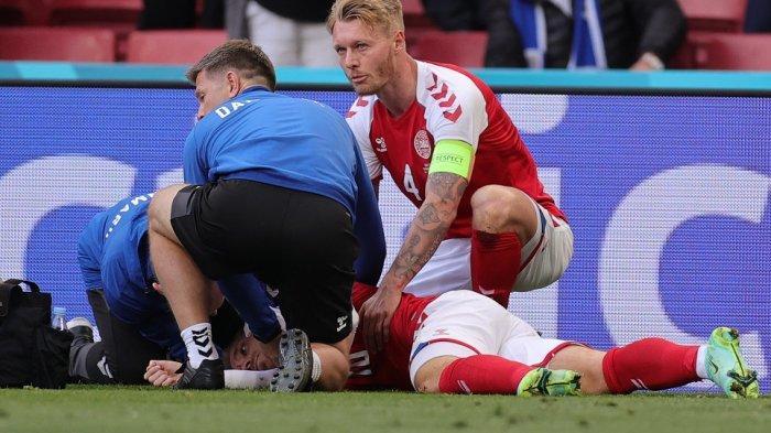 Gelandang Denmark Christian Eriksen (bawah C) menerima perawatan medis setelah pingsan di lapangan pada pertandingan sepak bola Grup B UEFA EURO 2020 antara Denmark dan Finlandia di Stadion Parken di Kopenhagen Sabtu (12/6/2021)