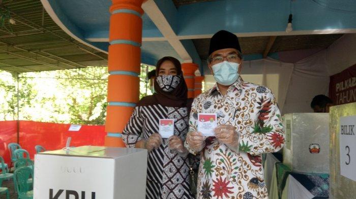 Calon Bupati nomor urut 1, Abdul Hali Muslih bersama dengan istri, menunjukkan suara suara saat mencoblos untuk Pilkada Bantul di TPS 006 Singosaren, Wukirsari, Imogiri, Bantul.
