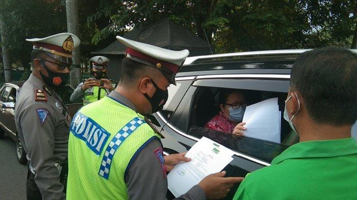 Petugas kepolisian mengecek surat-surat pengendara yang melintas di perbatasan Jateng-DIY di Prambanan, Klaten, Jumat (30/4/2021).