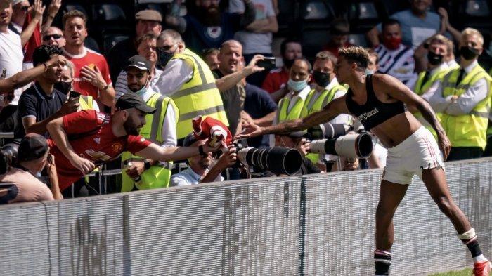 Jesse Lingard memberikan jerseynya pada pendukung Manchester United yang hadir pada uji tanding pra musim kontra Derby County, Minggu (18/7/2021).