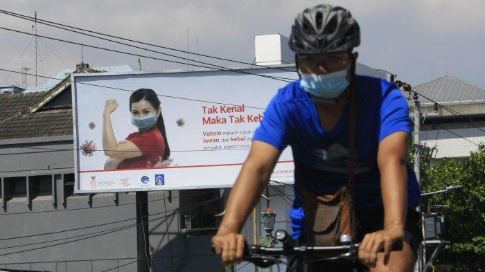 engguna jalan melintasi baliho sosialisasi tentang vaksin di Kota Yogyakarta, Jumat (13/11/2020).