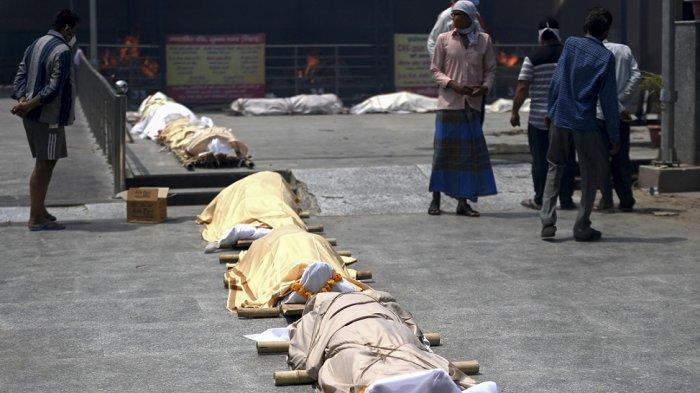 Orang-orang berdiri di dekat jenazah korban virus corona Covid-19 sebelum dikremasi di tempat kremasi di New Delhi 28 April 2021.