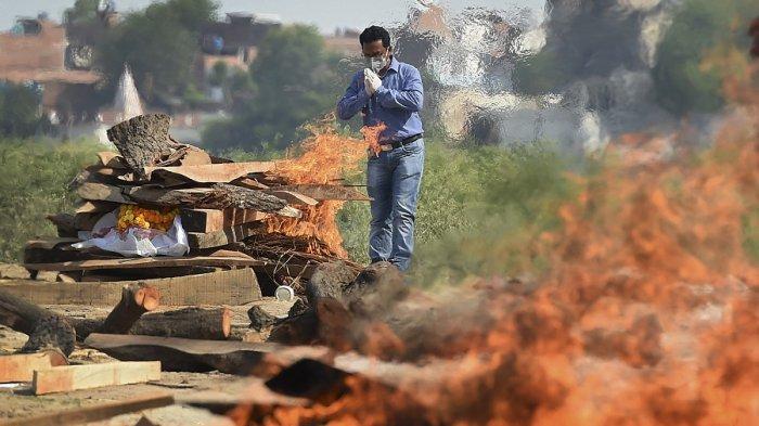 Seorang anggota keluarga berdoa pada saat proses  kremasi jenazah yang meninggal karena virus Corona Covid-19 di tempat kremasi di Allahabad pada 8 Mei 2021, Saatb itu India mencatat lebih dari 4.000 kematian akibat virus corona dalam sehari untuk pertama kalinya.