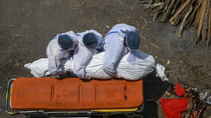 Petugas mengenakan perlengkapan APD (Personal Protection Equipment) membawa jenazah yang meninggal karena virus Corona Covid-19 di tempat kremasi di New Delhi, 27 April 2021.