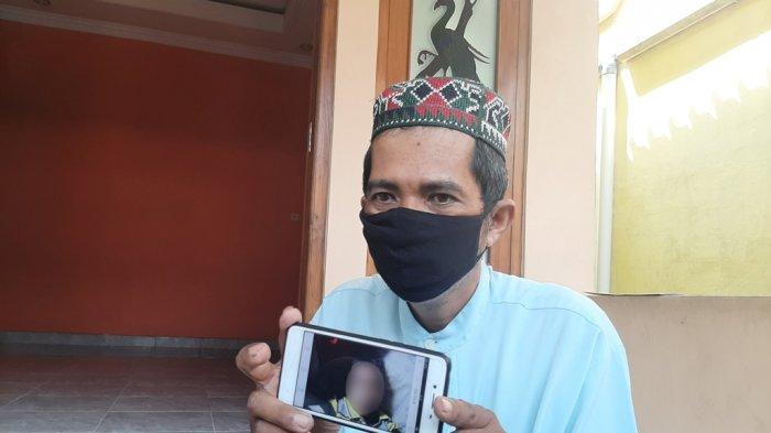 Bandiman memperlihatkan foto anaknya yang meninggal usai menyantap paket sate misterius, Senin (26/4/2021)
