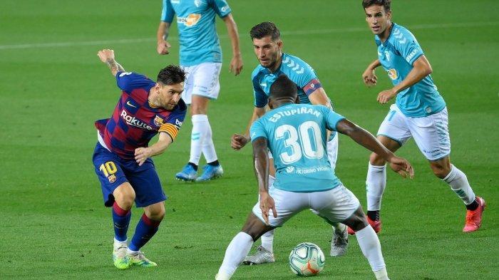 Lionel Messi (kiri) dihadang bek Osasuna Pervis Estupinan pada pertandingan Liga Spanyol antara FC Barcelona dan CA Osasuna di stadion Camp Nou di Barcelona pada 16 Juli 2020.