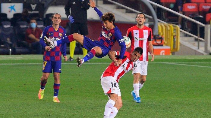 Gelandang Barcelona Riqui Puig melompati gelandang Athletic Bilbao Dani Garcia pada pertandingan sepak bola liga Spanyol antara FC Barcelona dan Athletic Club Bilbao di stadion Camp Nou di Barcelona pada 23 Juni 2020.
