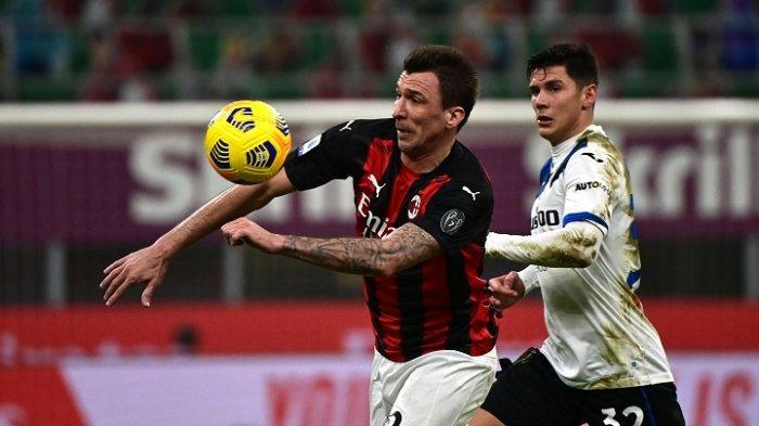 PenyerangAC Milan Mario Mandzukic (tengah) dan gelandang Atalanta Matteo Pessina berebut bola pada pertandingan sepak bola Serie A antara AC Milan vs Atalanta, Minggu 23 Januari 2021 di stadion San Siro di Milan.