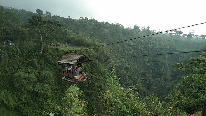 Pengunjung saat menaiki kereta gantung atau biasa disebut gondola yang menghubungkan Dusun Girpasang-Ngringin di Desa Tegalmulyo, Kecamatan Kemalang, Kabupaten Klaten, Selasa (19/1/2021).