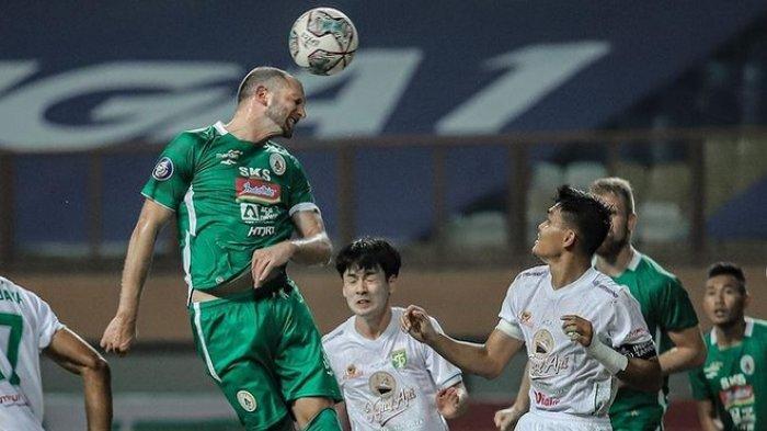 Striker asing PSS, Nemanja Kojic, mencoba menyundul bola ke gawang Persebaya.