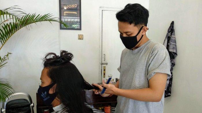 Ahmad Juanda (28), memangkas rambut pelanggan barbershop miliknya di Wonosari, Gunungkidul.