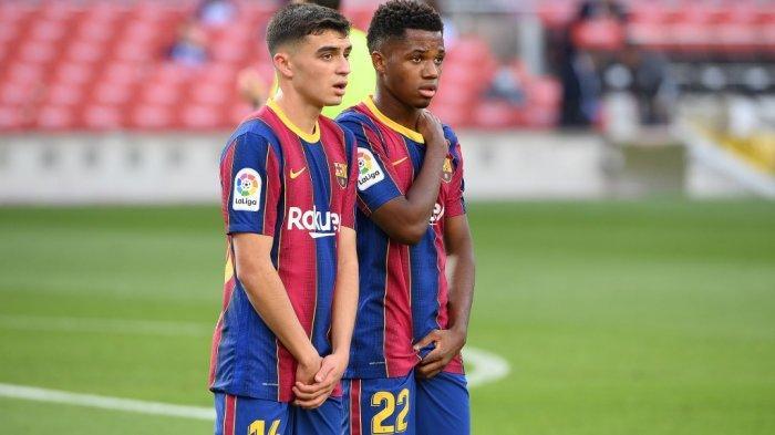Gelandang Spanyol Barcelona Pedri (kiri) dan gelandang Spanyol Barcelona Ansu Fati menghadiri pertandingan sepak bola Liga Spanyol antara Barcelona dan Real Madrid di stadion Camp Nou di Barcelona pada 24 Oktober 2020.