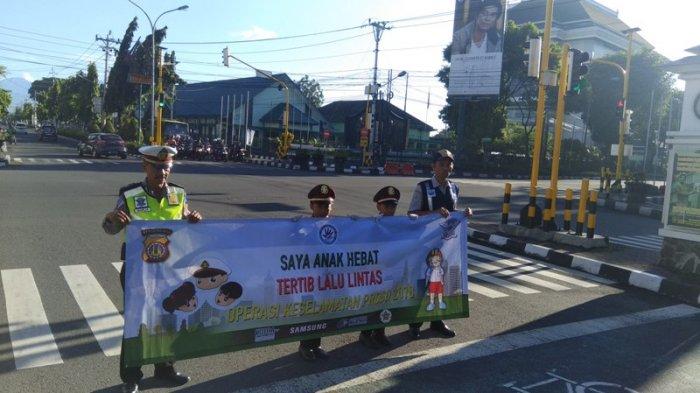 Ilustrasi : Kanit Dikyasa yang juga sebagai Kasatgas Preemtif Operasi Keselamatan Progo 2018 Satlantas Polresta Yogyakarta, Iptu Marija, bersama Pocil membentangkan Spanduk keselamatan di simpang empat Gramedia