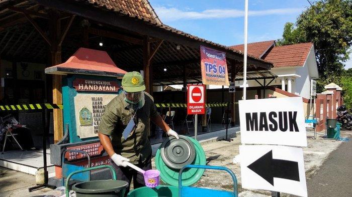Petugas Linmas menyiapkan air untuk cuci tangan di TPS 04 Purbosari, Wonosari, Gunungkidul pada Rabu (09/12/2020) lalu.