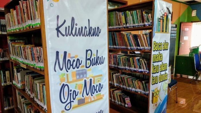 Rak-rak yang penuh berisi koleksi buku dalam ruangan Perpusdes Pengkol, lengkap dengan kata-kata motivasi meningkatkan minat baca.