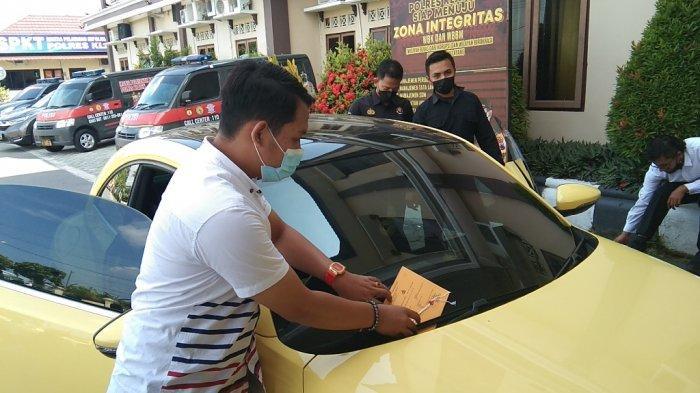 Personel Polres Klaten memasang tanda barang bukti di mobil VW kuning viral sesaat sebelum jumpa per di Mapolres setempat, Senin (10/5/2021).