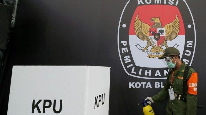 Petugas Linmas menyemprotkan cairan disinfektan ke area Tempat Pemungutan Suara (TPS) saat simulasi pemungutan suara Pilkada serentak di Alun-Alun Kota Blitar, Jawa Timur, Kamis (3/12/2020).