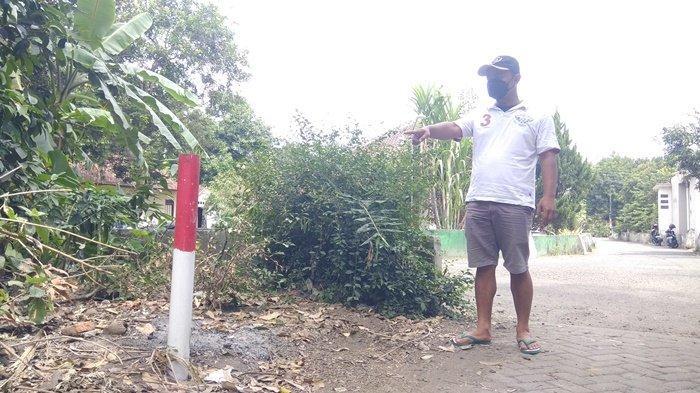 Jogoboyo (Kasi Pemerintahan) Tirtoadi, yang juga menjabat Plt Dukuh Sanggrahan, Heky Prihantoro, menunjukkan patok proyek tol Jogja - Bawen di Sanggrahan, Sleman