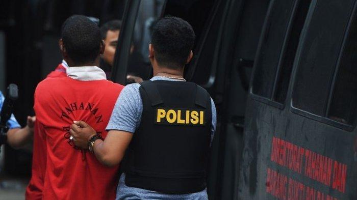 Polisi menggiring salah satu tersangka kasus unjuk rasa yang berujung rusuh di Papua ketika olah TKP di Kota Jayapura, Papua, Minggu (1/9/2019).