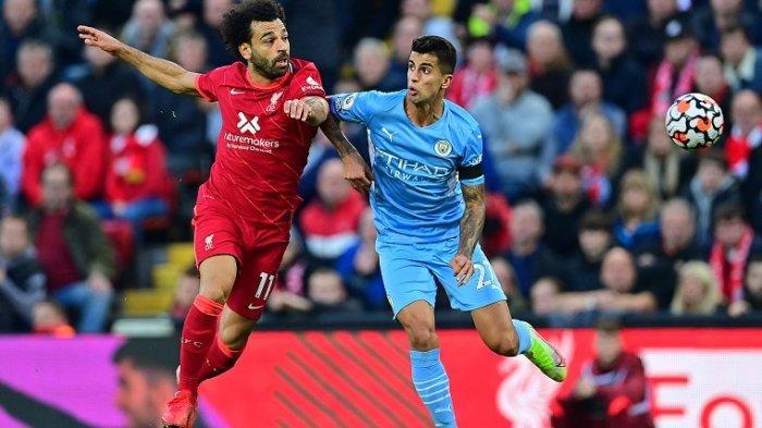 Gelandang Liverpool Mesir Mohamed Salah (kiri) adu kuat dengan gelandang Manchester City Rodrigo pada pertandingan sepak bola Liga Premier Inggris antara Liverpool dan Manchester City di Anfield di Liverpool, Minggu 3 Oktober 2021.