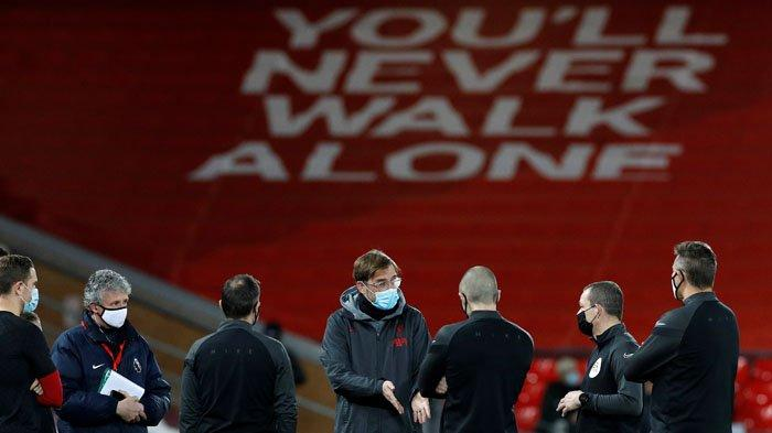 Manajer Liverpool Jurgen Klopp (tengah), mengenakan masker atau penutup wajah berbicara dengan para petugas menjelang pertandingan sepak bola Liga Premier Inggris antara Liverpool dan Brighton dan Hove Albion di Anfield di Liverpool, Kamis 4 Februari 2021.