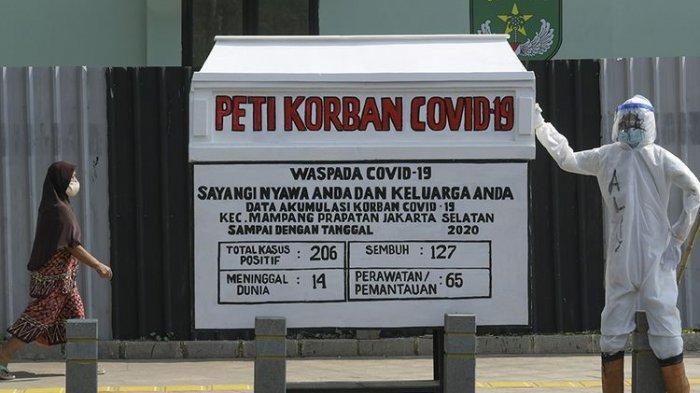 Warga melintas di samping replika peti mati dengan petugas yang menggunakan APD di kawasan Kemang, Jakarta, Minggu (16/8/2020). Kegiatan tersebut untuk menyosialisasikan bahaya Covid-19 yang dapat menyebabkan kematian.