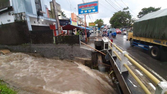 Saluran Irigasi Legok di Jalan Jenderal Sarwo Edi Wibowo, tepatnya di Dusun Sekaran, Desa Banyurojo, Kecamatan Mertoyudan, Kabupaten Magelang, meluap, Rabu (6/1/2021). Air menggenang tinggi sampai ke jalan. Satu gerobak PKL rusak berat karena hanyut terbawa banjir.