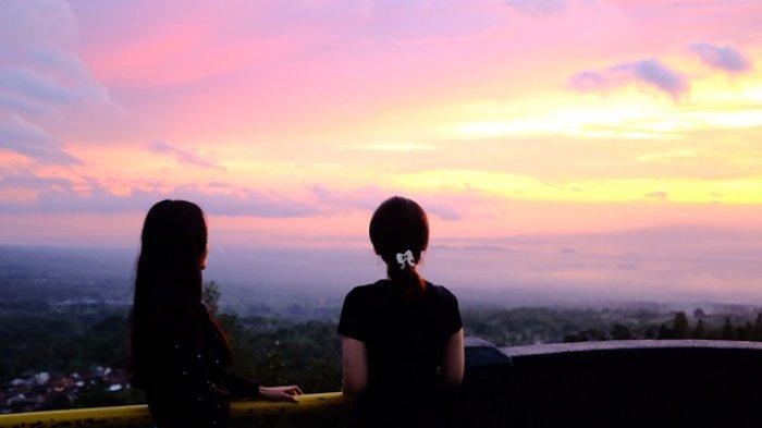 Wisatawan menikmati pemandangan matahari terbenam di Ketep Pass, Sawangan, Magelang, Sabtu (8/2/2020).