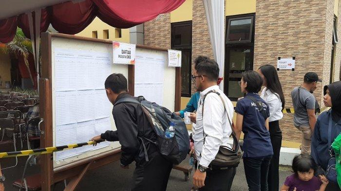 Peserta CPNS melihat pengumuman dan  jadwal sesi ujian SKD Calon Pegawai Negeri Sipil (CPNS)