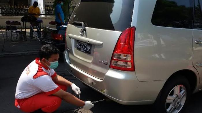 Ilustrasi : Petugas sedang mencatat kadar HC dan CO di mesin pengukur emisi di