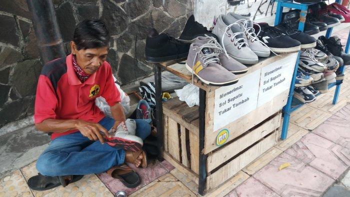 Tak pernah mengeluh- Wardiman (60) tukang sol sepatu di jalan Kranggan, kota Yogyakarta sedang memperbaiki sepatu pelanggan pada Senin (12/10/2020).